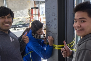 Freshman Alberto Escobar-Ruiz and Freshman Tung Anh Cao look on as a fellow classmate signs the exposed support beam.