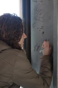 Senior Loren Crawford signs one of the exposed beams. Photo by Bekah Colbert.