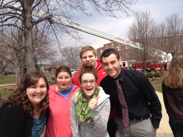 "Shelby Delaney and her friends gather to take a ""selfie"" with the firetruck in the quad. A large crowd of onlookers stood outside the library and applauded as firefighters exited the building. Photo by A.E. Sarver."